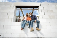 Familie im Fenster eines Bausatzhauses